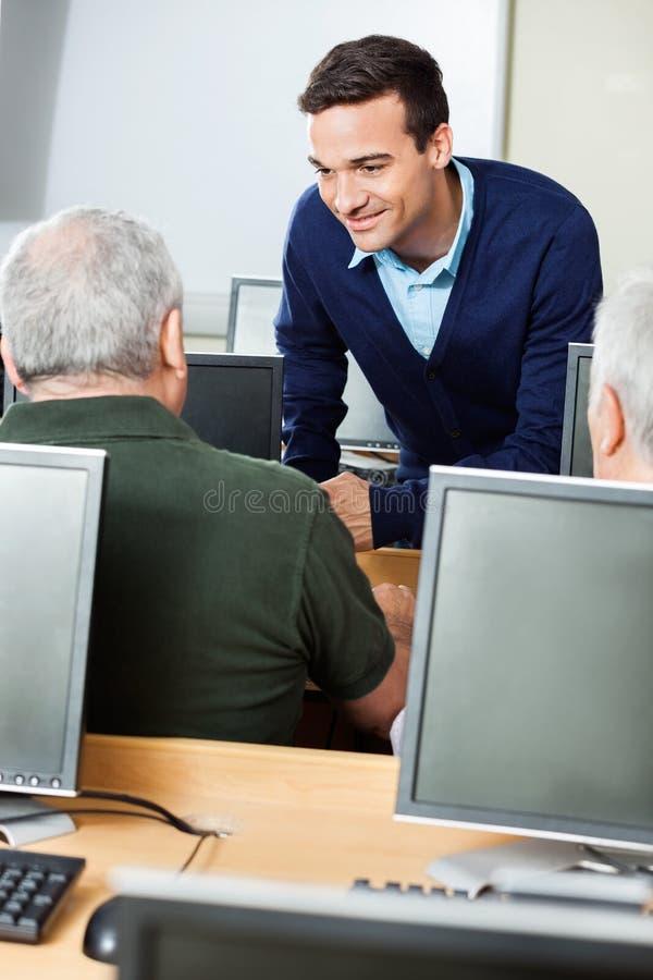 Lycklig lärare Assisting Senior Student i datorklassrum arkivbild