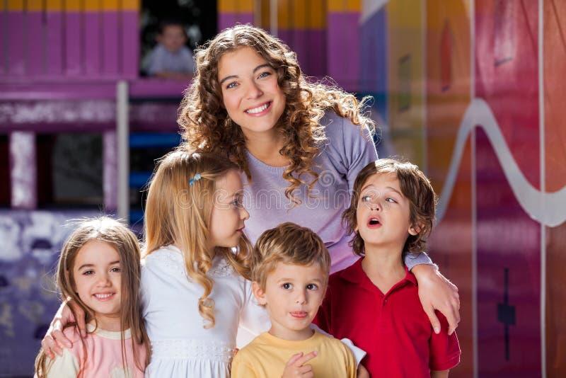Lycklig lärare With Cute Children i förträning arkivfoto