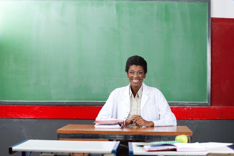 Lycklig lärare Sitting At Desk i klassrum royaltyfri fotografi