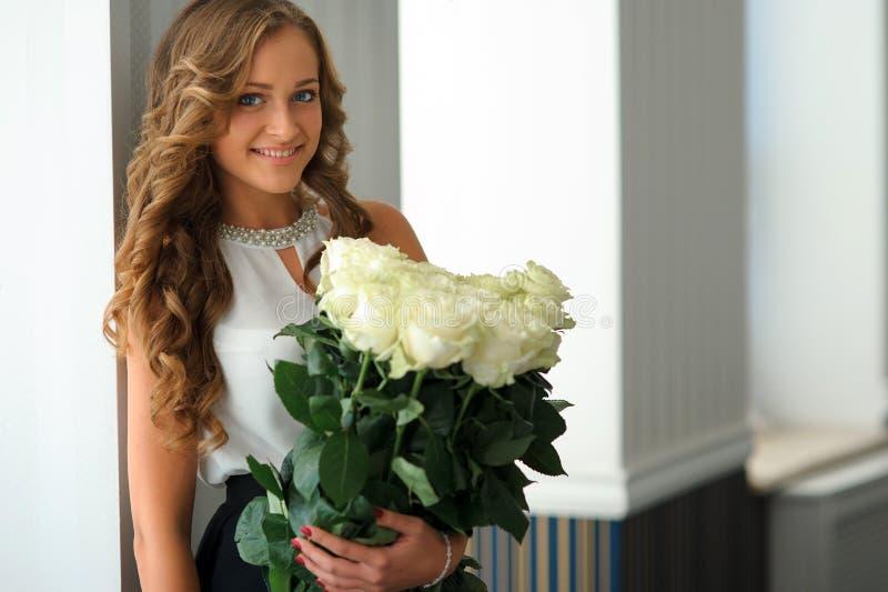 Lycklig lång hårung flicka med en bukett av vita rosor inomhus royaltyfri foto