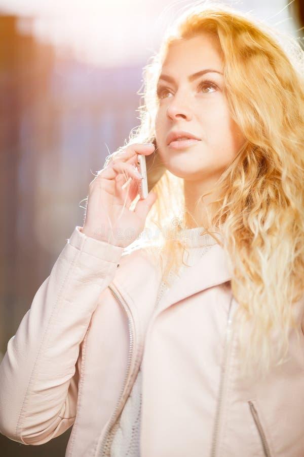 Lycklig långhårig blondin med telefonen royaltyfria bilder