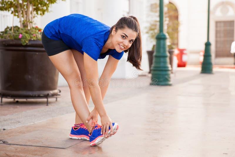 Lycklig löpare som sträcker henne ben arkivfoton