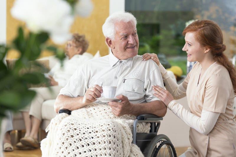 Lycklig lam hög man i en rullstol som dricker te och en ca royaltyfri foto