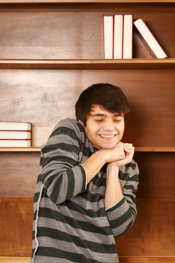 Lycklig latino-asiat man framme av bokhyllan arkivfoton