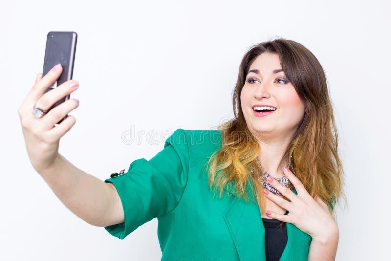 Lycklig le affärskvinna som bär i det gröna omslaget som tar selfie, den ljusa bilden av den lyckliga och le kvinnan royaltyfria foton