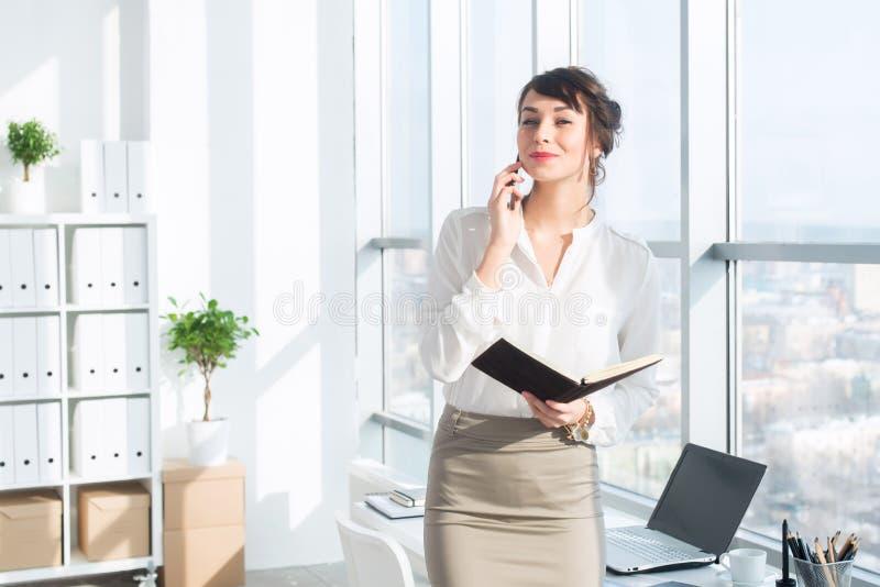 Lycklig le affärskvinna som har en affärsappell och att diskutera möten och att planera hennes arbetsdag, genom att använda smart royaltyfria bilder