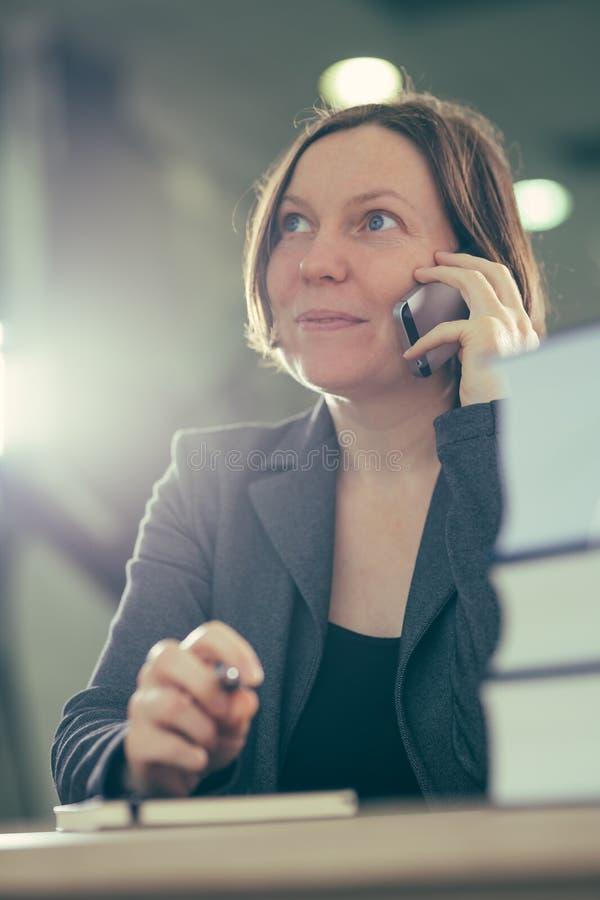 Lycklig le affärskvinna som talar på mobiltelefonen arkivbild