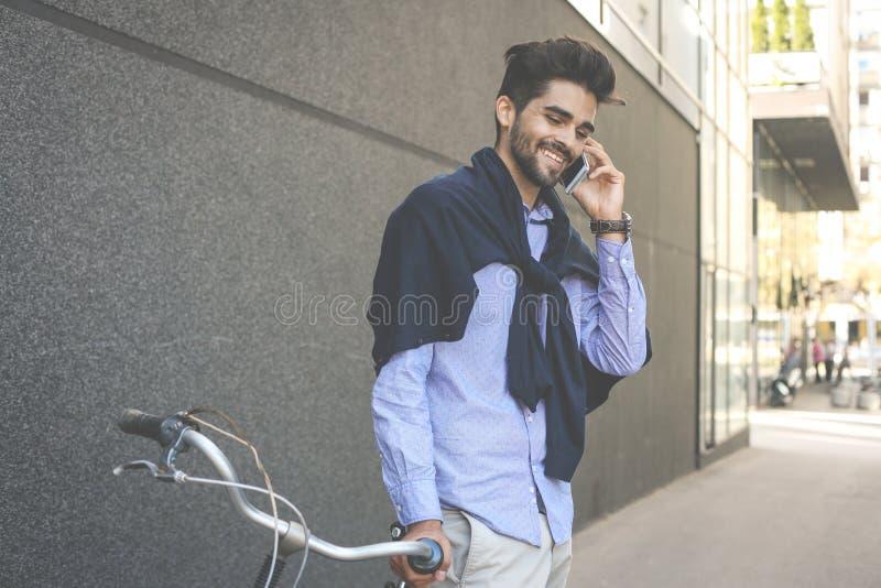 Lycklig le affärsman på cykeln i gatan som har konversation royaltyfria foton