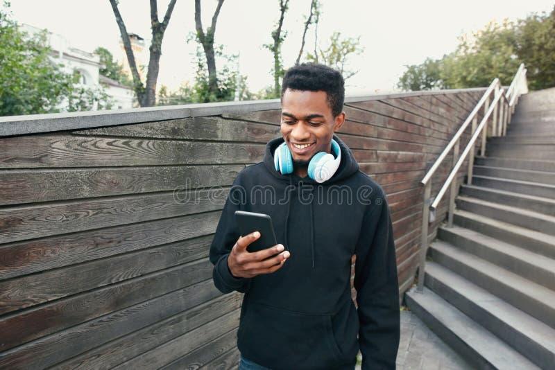 Lycklig le afrikansk man för stående med telefonen, hörlurar som lyssnar till musik som bär den svarta hoodien som går på stad arkivbilder