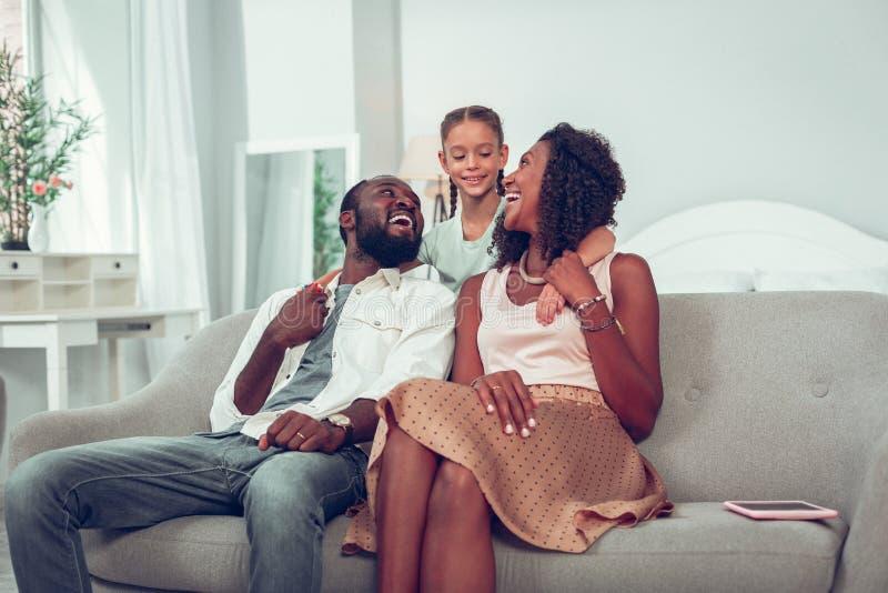 Lycklig le Afro--amerikan familj av tre som sitter på soffan royaltyfria foton