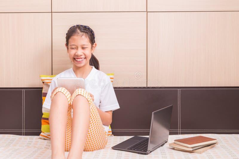 Lycklig le asiatisk flicka som använder minnestavladatoren för att studera på hennes b arkivbilder