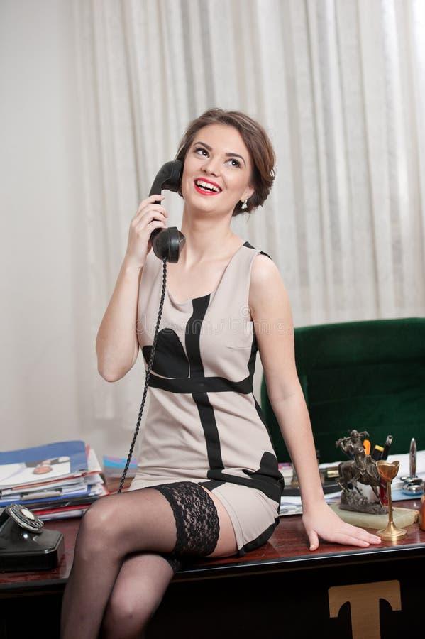 Lycklig le attraktiv kvinna som bär en elegant klänning och svarta strumpor som talar vid telefonen i ett kontorslandskap härlig  royaltyfri bild