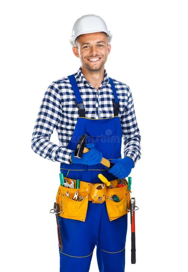 Lycklig le byggnadsarbetare med hammare- och hjälpmedelbältet arkivfoto