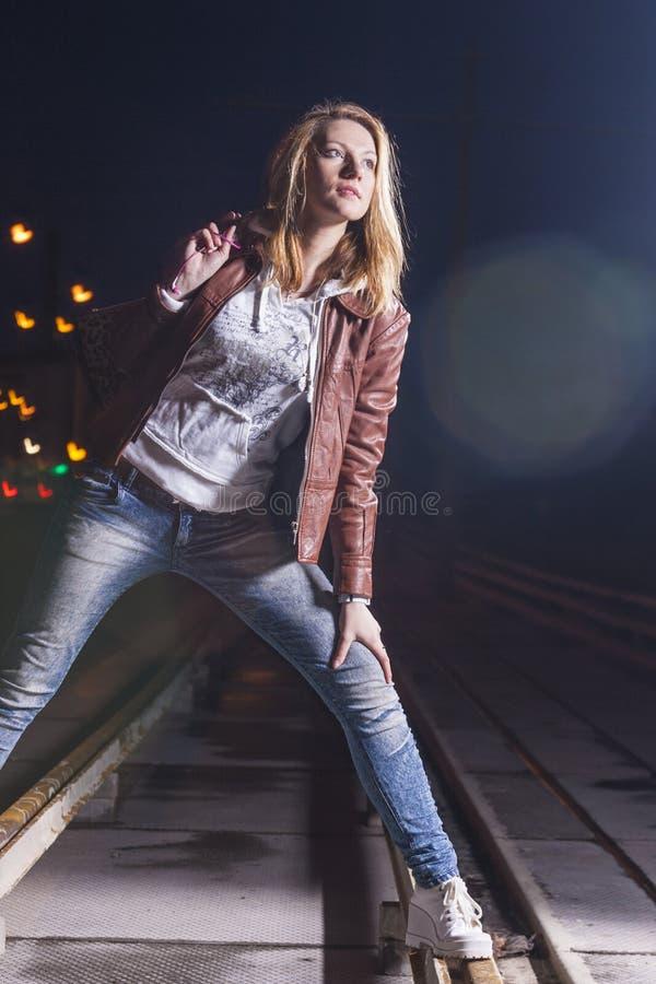 Lycklig le Caucasian kvinna i läderomslaget och jeans som utomhus spelar på stänger med påsen på natten royaltyfria bilder