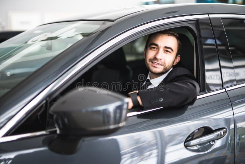 Lycklig le chaufför i bilen, stående av den unga lyckade affärsmannen arkivbild