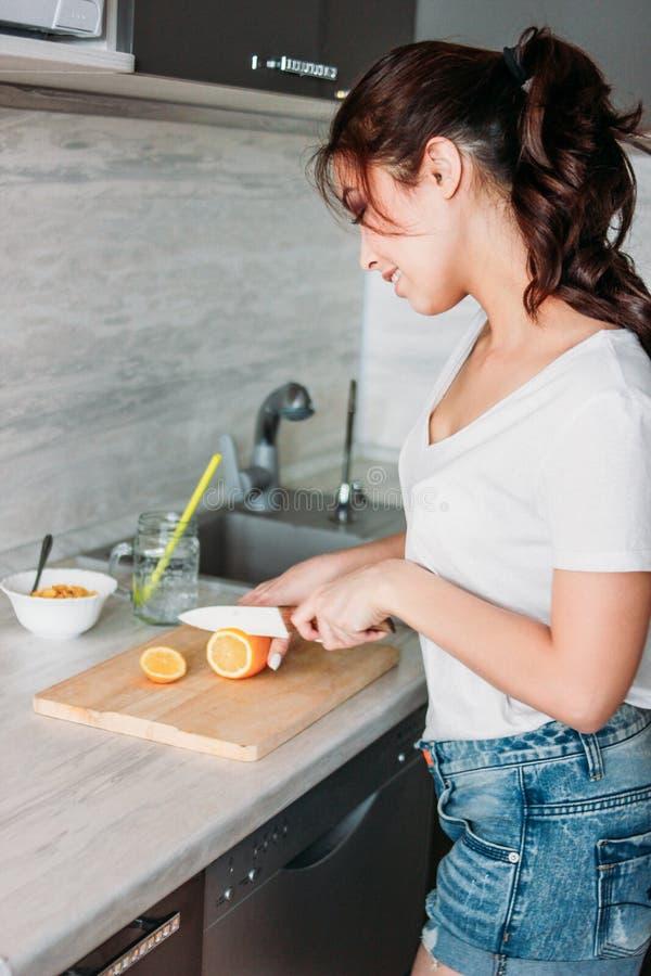 Lycklig le citron för snitt för ung kvinna för flicka för härligt långt hår asiatisk i hennes kök fotografering för bildbyråer
