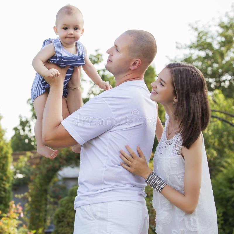 Lycklig le familj av den härliga brunettmodern för slank passform som är djärv royaltyfria bilder