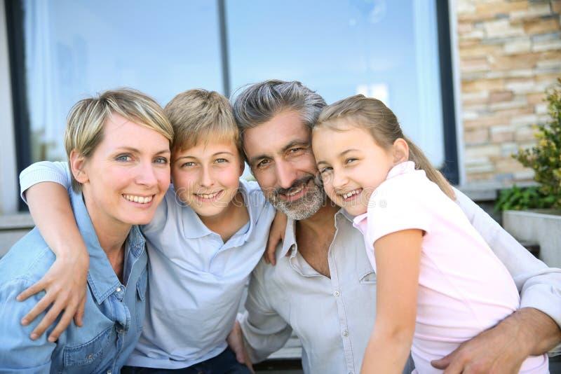 Lycklig le familj framme av deras nya hem arkivfoton