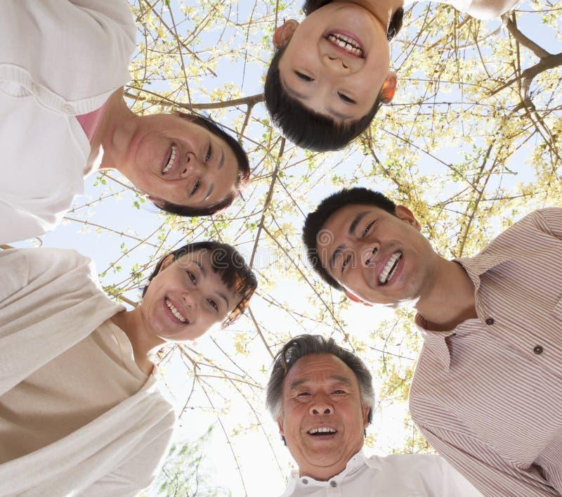Lycklig le familj i en cirkel som ser ner i en parkera i våren royaltyfria foton