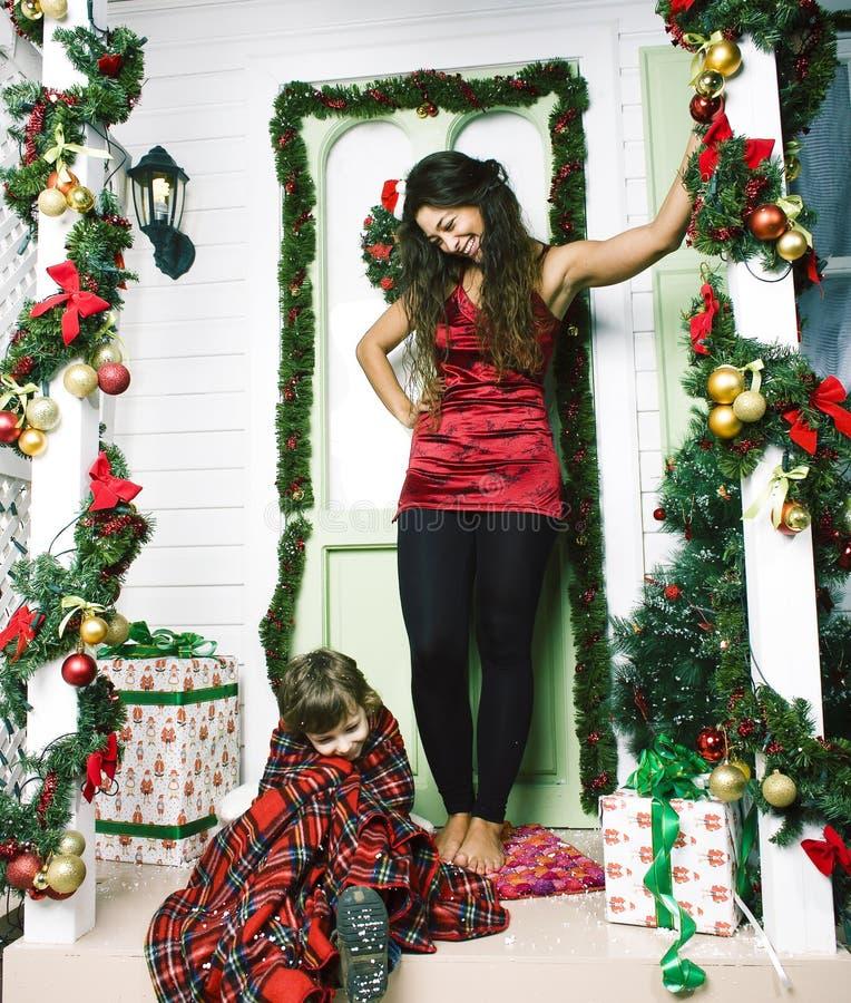 Lycklig le familj p? jul p? huset med g?vor, barnmodern och den lilla sonen i Santas den r?da hatten, livsstilferie arkivfoton