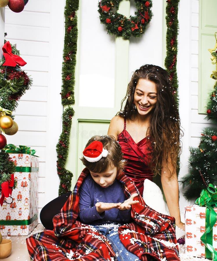 Lycklig le familj p? jul p? huset med g?vor, barnmodern och den lilla sonen i Santas den r?da hatten, livsstilferie arkivbild