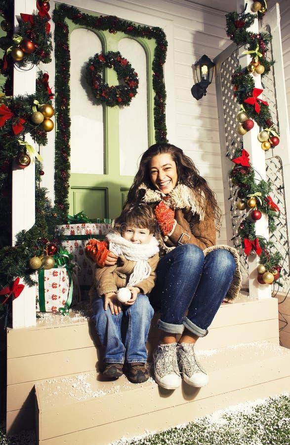 Lycklig le familj p? jul p? huset med g?vor, barnmodern och den lilla sonen i Santas den r?da hatten, livsstilferie royaltyfri fotografi