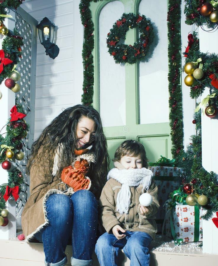 Lycklig le familj p? jul p? huset med g?vor, barnmodern och den lilla sonen i Santas den r?da hatten, livsstilferie arkivfoto