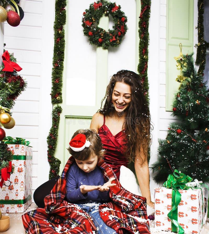 Lycklig le familj p? jul p? huset med g?vor, barnmodern och den lilla sonen i Santas den r?da hatten, livsstilferie arkivbilder
