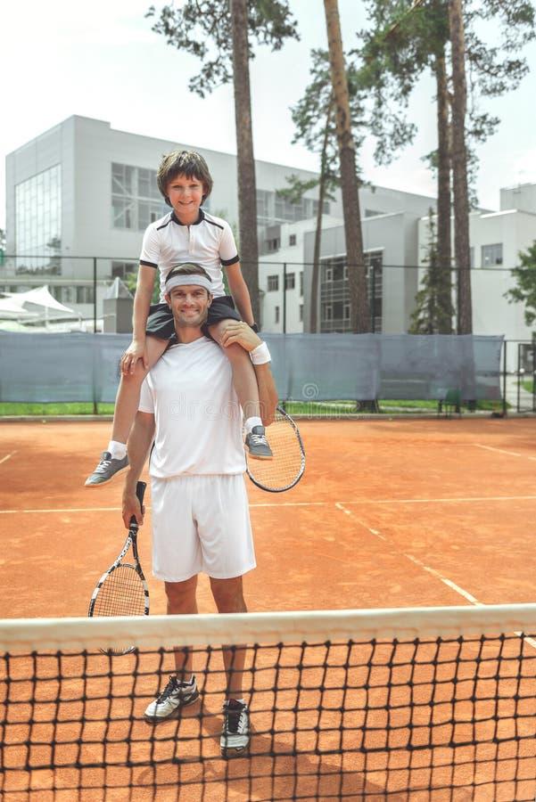 Lycklig le familj som lokaliserar nära tennisraster arkivfoton