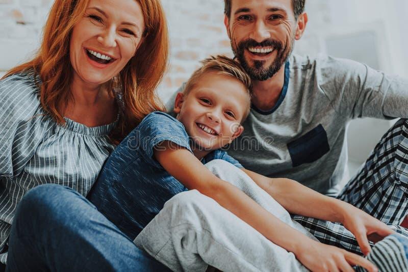 Lycklig le familj som tillsammans hemma kopplar av royaltyfri fotografi