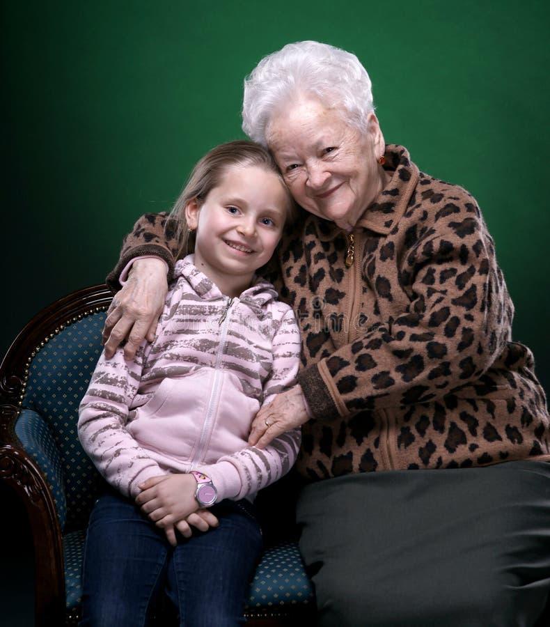 Lycklig le farmor och sondotter som poserar i studio royaltyfri fotografi