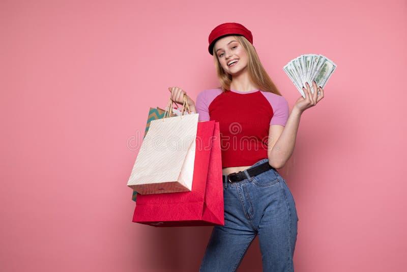 Lycklig le flicka i den moderiktiga r?da hatten som rymmer f?rgrika shoppa p?sar royaltyfri bild