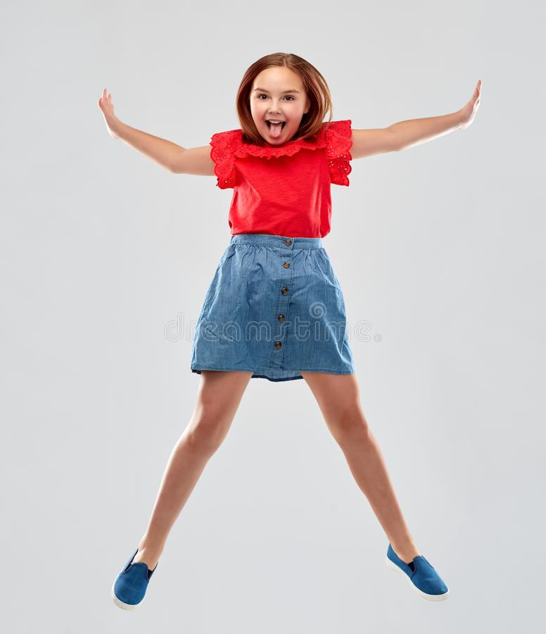 Lycklig le flicka i r?tt hoppa f?r skjorta och f?r kjol fotografering för bildbyråer