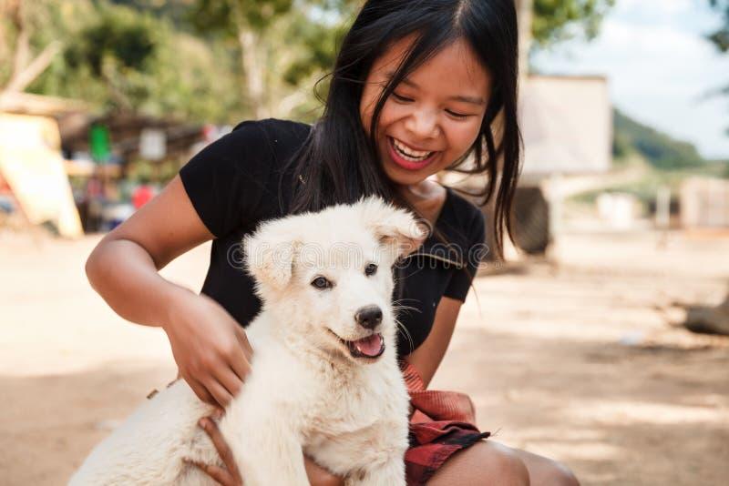 Lycklig le flicka som rymmer en vit hundvalp i hennes hand utomhus- arkivbild