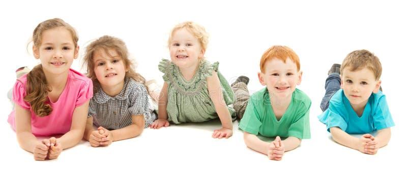 Lycklig le grupp av ungar på golv royaltyfria foton