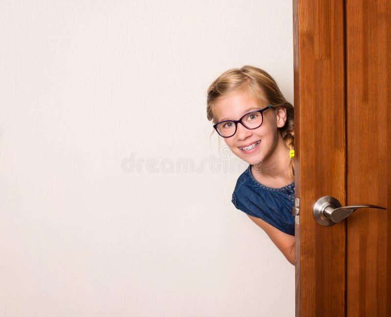 Lycklig le gullig flicka i glasögon bak dörr hemma royaltyfria foton