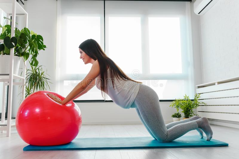 Lycklig le härlig gravid kvinna som hemma övar med pilatesbollen fotografering för bildbyråer