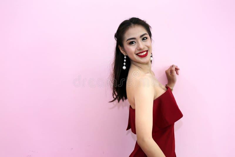 Lycklig le härlig ung sexig kvinna i röd partiklänning arkivbild