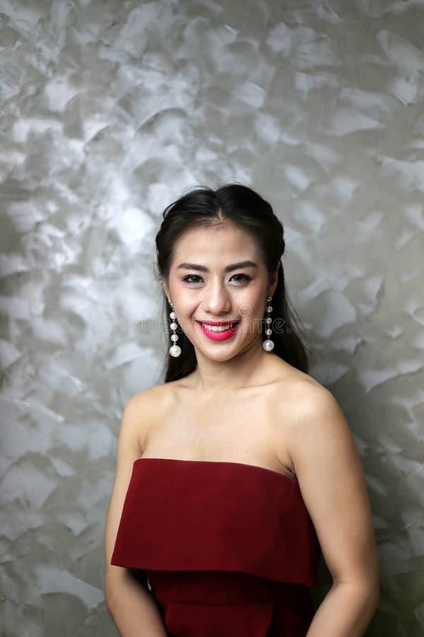 Lycklig le härlig ung sexig kvinna i röd partiklänning royaltyfria bilder