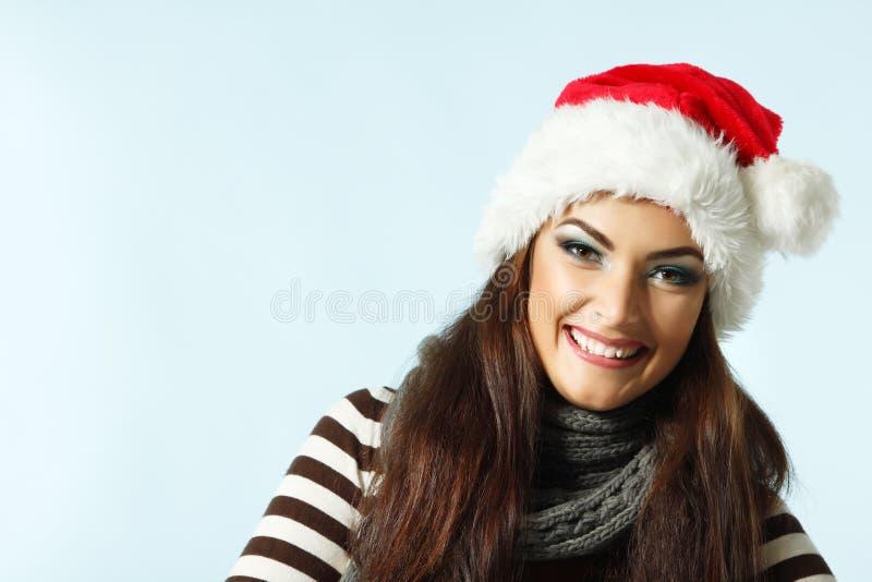 Lycklig le julkvinna i santas röda hatt, vinterflicka ov arkivfoto