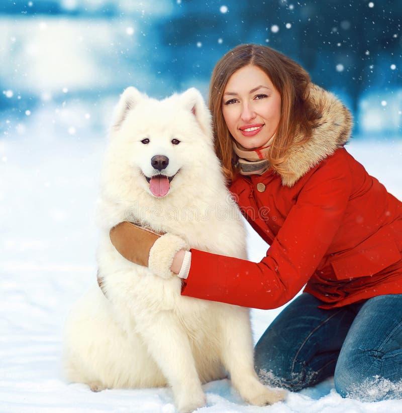 Lycklig le kvinna för julstående med den vita Samoyedhunden på insnöad vinterdag royaltyfri foto