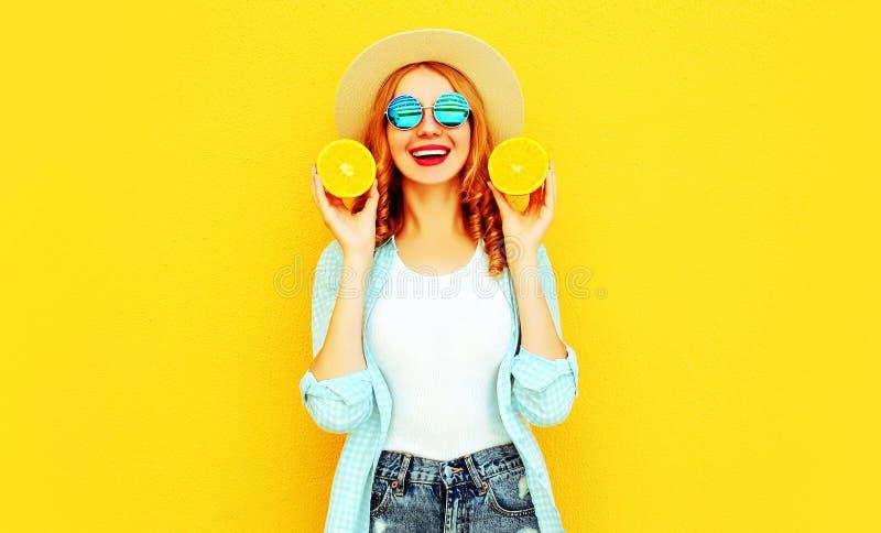 Lycklig le kvinna för sommarstående som rymmer i hennes handskivor av apelsinen i sugrörhatt på färgrik guling arkivfoton