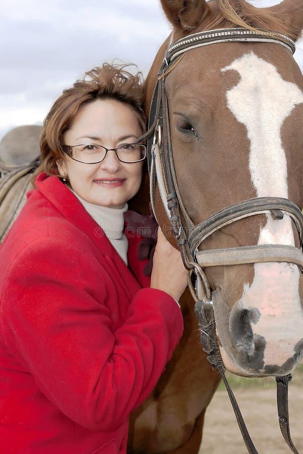 Lycklig le kvinna för stående med hästen arkivbilder