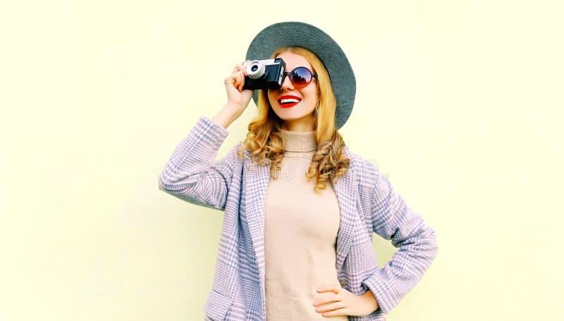 Lycklig le kvinna för ståendenärbild som rymmer den retro kameran som tar bilden som bär det rosa laget fotografering för bildbyråer