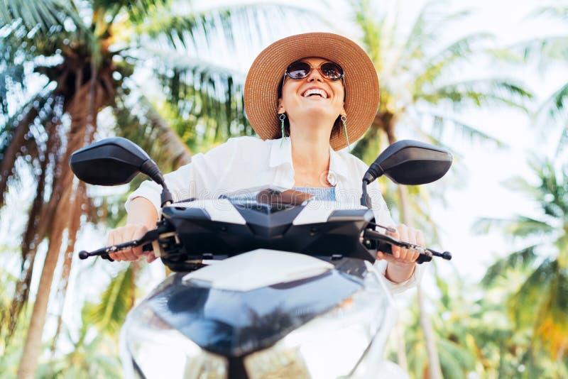 Lycklig le kvinna i sugrörhatt och solglasögon som rider mopeden under palmträdet royaltyfri fotografi