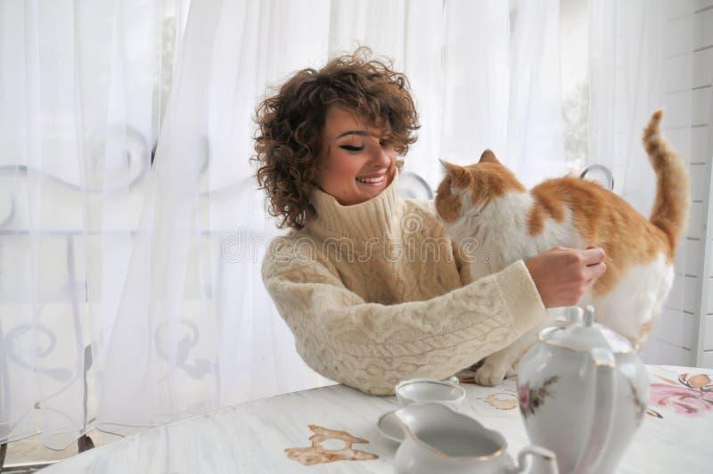 Lycklig le kvinna i varmt tröjasammanträde på tabellen, keln och innehavet en katt hemma arkivfoton