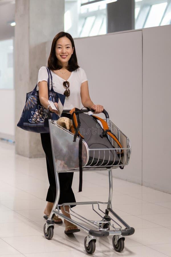 Lycklig le kvinna med bagage i vagn på flygplatsen arkivbild
