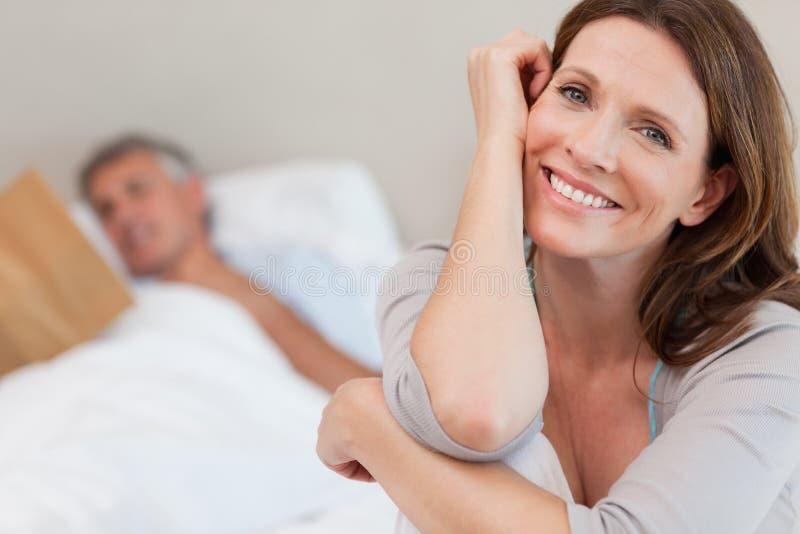 Lycklig le kvinna på säng med makaläsning bak henne arkivfoton