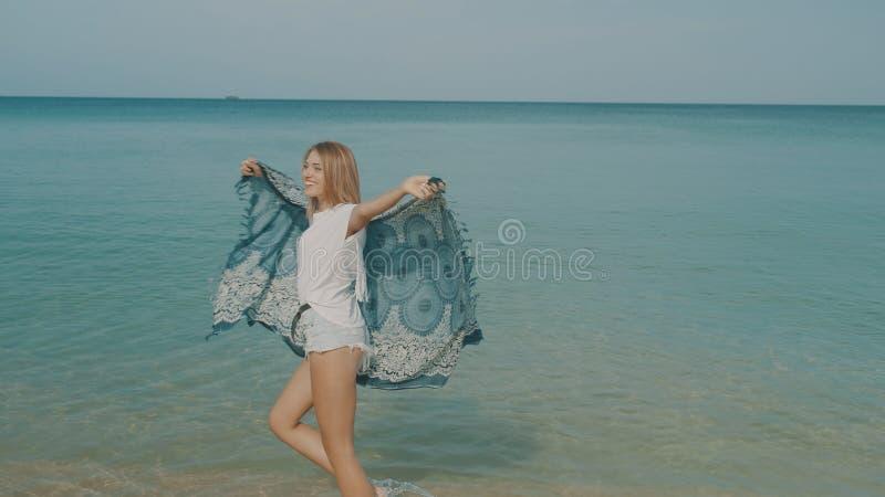 Lycklig le kvinna på stranden royaltyfria foton
