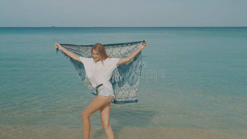 Lycklig le kvinna på stranden arkivbild